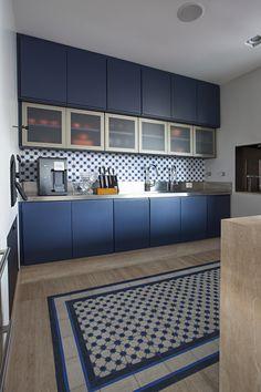 """O profissional optou por um décor alegre, com tons de azul e laranja. O ladrilho hidráulico aparece na bancada e no piso, parecendo um tapete. """"Como a família gosta de tudo prático e limpo, usar um tapete de verdade quebraria a rotina da casa, devido a sua manutenção. Então desenhamos no mármore o espaço para entrar com o ladrilho dando charme e personalidade para a decoração"""", explica Bruno."""