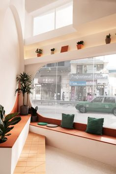 A corner of casual, stepped bench seating topped with terracotta tiles is dotted with potted plants and framed by a semi-circular mural in this Hong Kong cafe. Arch Interior, Cafe Interior, Interior Architecture, Interior Design, Hong Kong Cafe, Colorful Cafe, Banquet Seating, Old Apartments, Small Space Organization