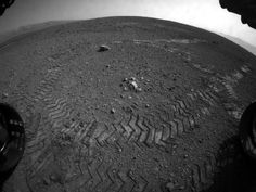 This image shows the tracks left by NASA's Curiosity rover on Aug. 22, 2012, as it completed its first test drive on Mars. The rover went forward 15 feet (4.5 meters), rotated 120 degrees and then reversed 8.2 feet (2.5 meters). Curiosity is now 20 feet (6 meters) from its landing site, named Bradbury Landing.     This image was taken by a front Hazard-Avoidance camera, which has a fisheye lens.     Image credit: NASA/JPL-Caltech