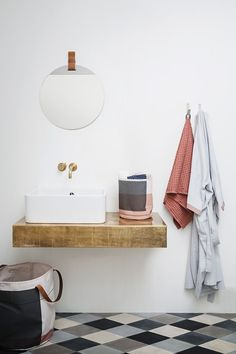 thick wood floating vanity, white vessel sink, brass wall mount faucet, patterned floor
