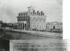 """Early Denver Schoolone of the original schools in Denver, Colorado. The picture was taken from across the street and the three stories of the building as well as the white picket fenced yard can be seen. Students are gathered in the yard around the school and on the balcony over the main entrance. Caption attached to bottom of photo reads: """"Breaking Ground on the Denver Pacific Railroad-May 18th 1868. Near what is now the D.P. and K.P. Junction  :: Creating Your Community - Denver Public…"""