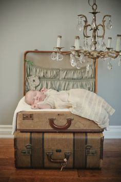 Beautiful baby portrait by Sadie Olive www.sadieolive.com/  --  This idea could work well for a First Birthday shoot, too. I'd use a more colorful backdrop and eliminate the chandelier. Also, consider placing some of baby's favorite items in the suitcase pockets.