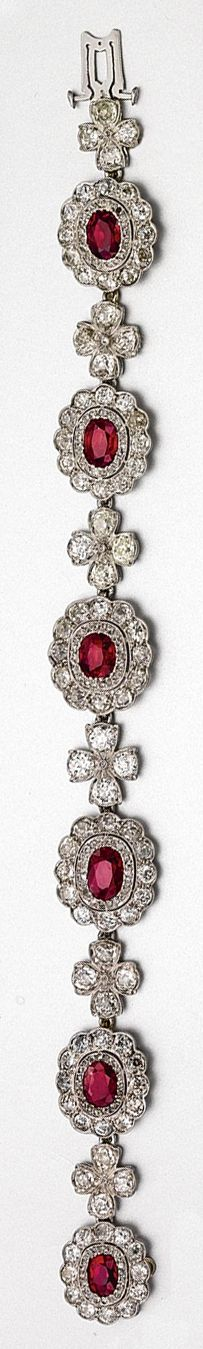 RUBY AND DIAMOND BRACELET.  Composed of six floral medallions spaced by links of clover design, set with 6 oval-shaped rubies and with 96 old European-cut diamonds weighing approximately 9.60 carats, mounted in platinum, length 7 inches.