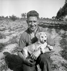Vintage Photos: Harold Gear Paton. New Zealander G J Lewis  holding the dog named Trip Trip, the unit pet, 9 March 1943