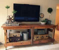 Rustic industrial workbench turned entertainment center. I love the antique suitcases too!