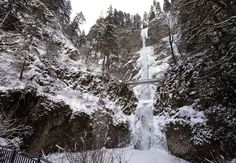 Snow and ice coats the cliff walls and ground surrounding Multnomah Falls east of Portland on Friday. (Don Ryan / The Associated Press)