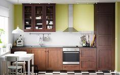 Traditionellt brunt kök med vitrinluckor, mörka bänkskivor och vitvaror i rostfritt stål