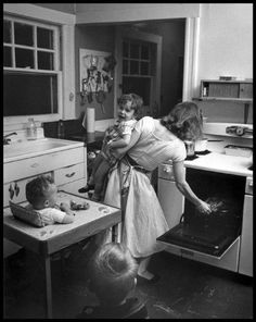 Elliott Erwitt | New Rochelle, NY, 1955 A nice domestic scene with his wife and kids. Erwitt's son Misha interviewed him about this photo: Misha: You took a photograph in 1955 of our mother cooking dinner, her back to the camera. She has Ellen, who's crying, in one arm and she's reaching into the oven with the other. I 'm sitting behind them in a high chair and there's another kid standing, watching.