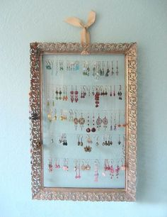 Organize your earrings with an old frame and some fishing wire.