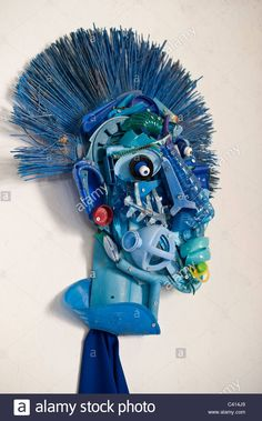 A blue coloured Art sculpture of a face  made from plastic rubbish waste found on the beach at Borth Wales UK Stock Photo