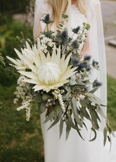 This bride carried a blue, white, and green Botanics of Melbourne bouquet, which stood out thanks to its huge protea and scattered thistle.