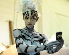 Body painting model Alexis Broker photographs herself before the show, as the Denver Fashion Weekend held it's day two fashion show which featured body painting at the EXDO Event Center in Denver on Friday, March 2, 2012. The body painting was carousel inspired. Cyrus McCrimmon, The Denver Post