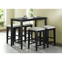 Enjoy delicious meals at home at this wooden black counter-height table which seats four. Its built-in footrest supports your feet while you're seated. The table's luxurious black grain finish contrasts nicely with lighter colored decor.