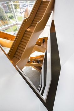 Grand orange staircase ascends through college by Saucier + Perrotte: