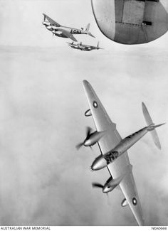 Qld. 1945-07-17. Three De Havilland (Australia) Mosquito fighter-bomber aircraft of No. 1 Squadron RAAF based at Amberley peel off echelon for an attack dive. Aircraft are A52-526 (coded NA-E), ...
