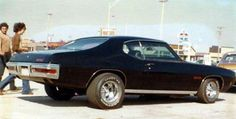 Just A Car Guy : Muscle cars in full effect, jacked in back with huge back tires and Cragars, Keystones, or slotted mags