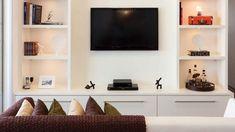 Estante de laca branca, com prateleiras para enfeites nas laterais da tv e base fechada. Projeto Andrea Pontes, via Tecto.