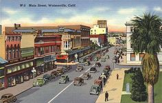 """An illustrated view of Main Street, Watsonville, CA, with the Hotel Resetar in the background. Printed on the front of the card, """"W-2 Main Street, Watsonville, CA"""".    Postmark Date: Unmarked  Distributor: Fulmer's, Santa Cruz, CA  Publisher: Unknown  From Back: """"Watsonville is the fast growing metropolis located in the center of Pajaro Valley.""""  C/O Santa Cruz Public Library"""