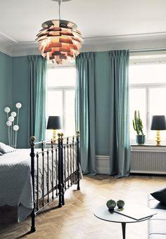 Elegant bedroom in blue shades featuring herringbone parquet flooring and the PH Artichoke Pendant in copper.