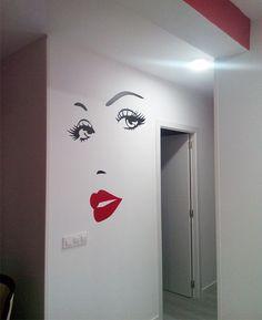 Vinilo decorativo de ojos y labios rojos, instalado en la pared de cliente. El resultado ha quedado muy elegante y fino.