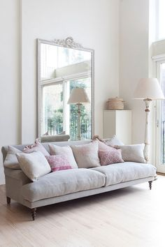 Love this soft pastel and white living room.  The clean modern look includes traditional elements such as the ornate gold mirror and sofa.  Beautiful pale hardwood floors.