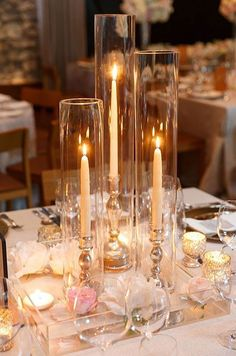 Alternating votive and taper candles is both beautiful and practical, allowing guests to interact across this simply chic reception table. The cylindrical vases will protect the candles from accidentally falling. #weddingcandlesdesign