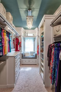 A long custom closet with built-in shelves for shoes and great storage . The blue ceiling and custom light fixture make it all seem very glamorous.
