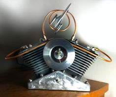 Straight from the chopping block.   This table lamp features two Harley Davidson cylinders (jugs) surrounded by a Screaming Eagle emblem holding the time. The copper lines create a flowing circle around a rocket 88 chrome emblem. The base is pounded out brushed aluminum with a toggle switch to fire up two 75 watt bulbs.
