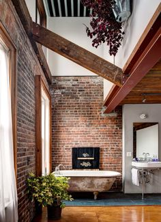 High-ceilinged Bathroom with exposed brick walls and beams