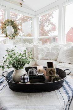 Farmhouse style coffee table in the sunroom - A lovely warm wood style coffee table style with a tablecloth on top to cozy it up. A great source for farmhouse & cottage style home decor! Love the fabric covered pumpkins!