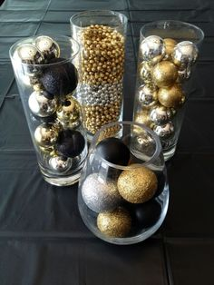 Gold, black, and silver Christmas ornaments in glass cylinders - Decoist