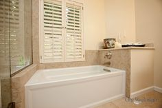 A step in tub is accented by the window and window covering.