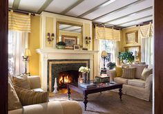 A warm living room with brick fireplace and upholstered sofa set also wooden table and pretty floor lamps decorated by soft yellow wall and window curtain treatment - PrivyHomes Yellow Walls Living Room, Four Square Homes, Living Room New York, Living Rooms, Ceiling Trim, Ceiling Beams, Ceilings, Best Leather Sofa, House On A Hill