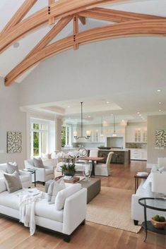 Great room with living room, dining area and white kitchen. Tall soaring ceiling with wood beams caps the living room area.