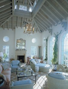 Spectacular garden room with super high ceilings, beaming, giant arched windows and rondelle windows, cream and peach floors, climbing ivy, and furniture in shades of blue, cream, and pink. Beyond prettiness (pretty sure this is Ferguson & Shamamian).