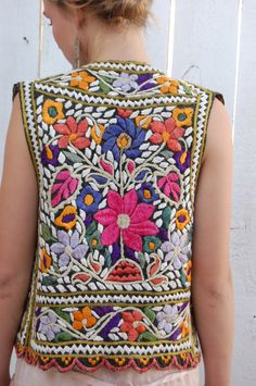 This vest is gorgeous! Beautiful colorful mexican style embroidery. Appears to be handmade. Dark gray background with white and vibrant shades of greens, purples, marigold and pink. Scalloped hem. You will adore it! Ive never seen anything quite like it. Make sure you see the up close pics. There are a few tiny loose threads and a small rust stain on the chest (I have not tried to remove it) but nothing that detracts from the beauty or will keep you from wearing it. Its so busy that you wont…