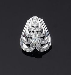 Mauboussin. c1935. Art Deco shield-shaped 3-tiered diamond brooch with pear shaped center. Set in platinum and white gold. 18 cts.
