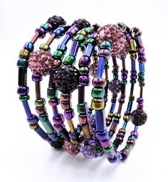 This whimsical jewel toned wrap bracelet is made on 6 rows of silver memory wire and consists of glass Czech beads, glass bugle beads, rectangular beads, and clay crystal disco ball beads in shades of lovely lavenders and purples with a rainbow iris finish on them. ★ Return to my main shop page here for more inventory ★ www.etsy.com/shop/bridgetollbeading ★ Read my FAQs below and if you have any further questions please do not hesitate to contact me! ★ https://www.etsy....