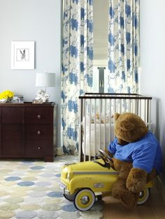 Fun blue & yellow boy's bedroom with pale blue walls paint color, white & blue floral curtains layered over white roman shades, blue & green dots rug and modern crib.