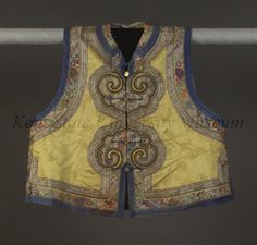 1870 Vest Culture: Chinese Medium: silk, satin Manchu Woman's Informal Domestic Vest (majia). Lemon yellow silk vest with center front opening, embroidered with bands laid in large scrolls and edged with blue satin.