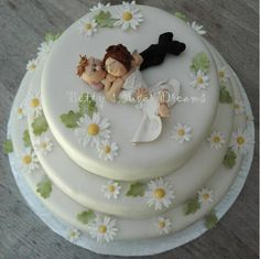 Cake covered with fondant and the daisies are made from gumpaste. the figures are made from polymer.