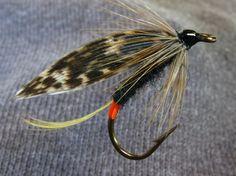 91)-Darling- Tag, orange floss, Tail, golden pheasant crest, Body, black dubbing, Wing, mottled turkey, Front hackle, soft furnace (hen).