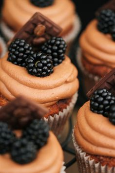 Nut and coffee cupcakes with chocolate cream and blackberries.