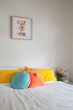 The couple's bedroom features embroidery art above the bed and cushion by local Australian maker Rachel Castle.