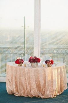 Glam sweetheart table idea - rose gold sequin linens with red flower centerpieces + ghost chairs {onelove photography}