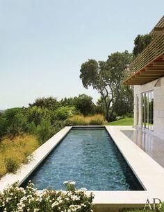 Limestone coping borders the lap pool | archdigest.com