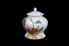Description A small compressed circular Chinese porcelain jar & cover. Decorated in colours with a crane perched upon a pine tree & amongst flowering peony on a ground, the cover with five black characters.  Date First half 20th century  www.collectorstrade.de