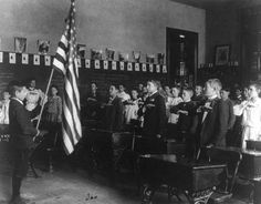 """Photo: students pledging to the flag, 1899, 8th Division, Washington, D.C. Credit: Frances Benjamin Johnston; Library of Congress, Prints and Photographs Division. Read more on the GenealogyBank blog: """"Flag Day: 'Under God' Added to Pledge of Allegiance."""" https://blog.genealogybank.com/flag-day-under-god-added-to-pledge-of-allegiance.html"""