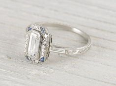 Art Deco vintage engagement ring made in platinum and centered with an approximate .90 carat EGL certified emerald cut diamond with E-F color and SI2 clarity. Circa 1920 Center diamond is accented by single cut diamonds and four triangle cut sapphires as well as two baguette cut diamonds on the shoulder. A feminine, thin band with stunning hand engraving throughout.Learn more about Art Deco rings Diamond and gold mining has caused devastation in areas such as Africa, wreaking havoc on…
