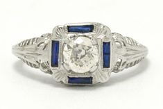The San Bernardino square antique Art Deco diamond engagement ring with a shimmering, sparkling half carat old European brilliant cut center. Filigree throughout and bordered by 4 calibre' sapphires in a geometric 18k white gold highlight this original setting. The experience of wearing an authentic circa 1920 Jazz Age treasure is sublime. #diamond #artdeco #engagementring #love #ido #diamonds #artdecoring #artdecorings #engagementrings #1920 #1920s #1920ring #1920sring Estate Engagement Ring, Antique Engagement Rings, Diamond Engagement Rings, Art Deco Ring, Art Deco Diamond, 1920s Ring, Gold Highlights, Jazz Age, Blue Sapphire Rings